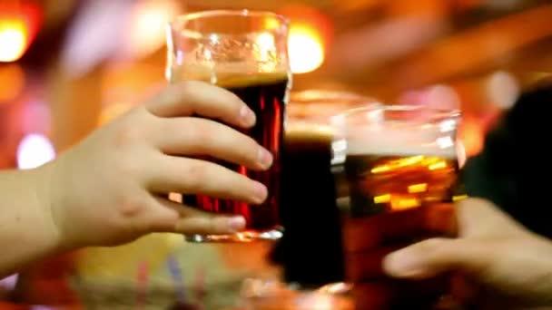 Három kéz összekoccannak szemüveg talpas pohár sör