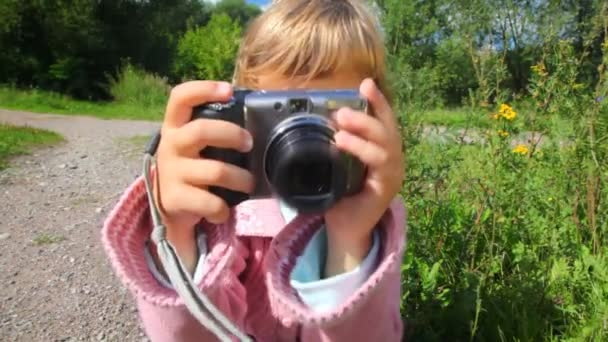 Porträt eines kleinen Mädchens mit Fotokamera im Park