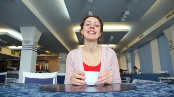 Woman drinks coffee in cafe