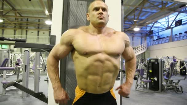 Bodybuilder straining muscles in gym
