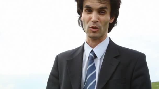 Angry handsome man in suit speaking to camera