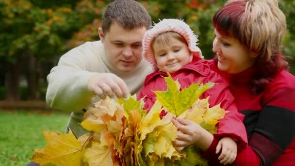 Muž, žena a holčička sbírat listí v podzimním parku