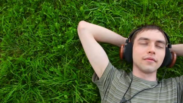 Fiatalember, hallgatni a zenét a fejhallgató feküdt a zöld fű, panoráma