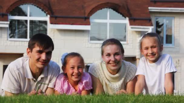 rodina s dvěma holčičkama leží na trávníku a úsměvy