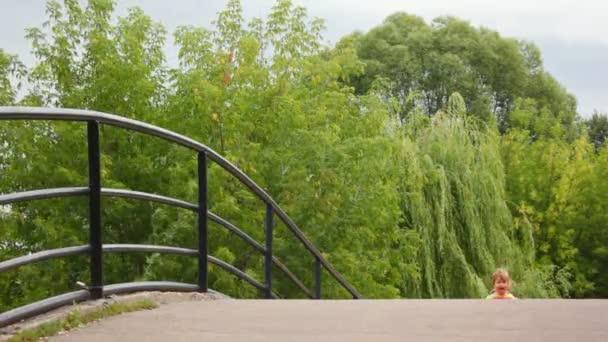děti se psem běží na mostě, k fotoaparátu