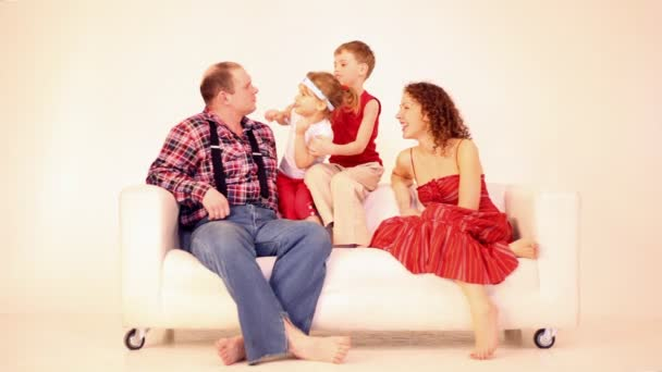 Family four with two children sit on sofa