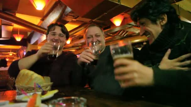 Three men clink glasses goblet with beer