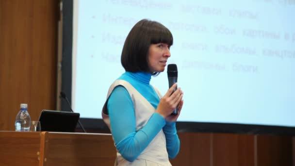 Nőről, aki beszél egy mikrofon, konferencia terem