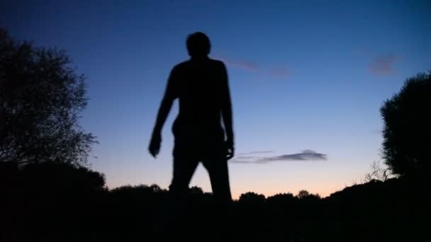 Man turning round on sunset background