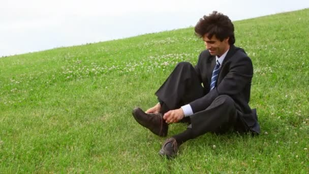 pohledný muž, sedící na zelené trávě a sundejte boty, ponožky