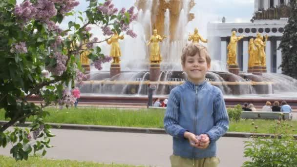 chlapec a dívka hraje a házení květů před sovětskou fontána
