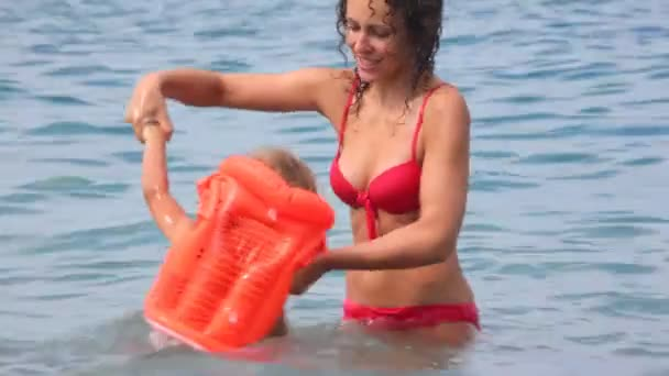 young woman and little girl in inflatable jacket has fun in water of sea