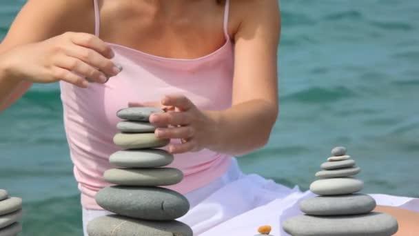 bezhlavé ženy stavební kámen zásobníku na oblázkové pláži, moře, v pozadí