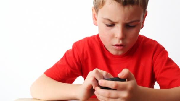 malé chlapce hrát v communicator s stylus na stole na bílém pozadí