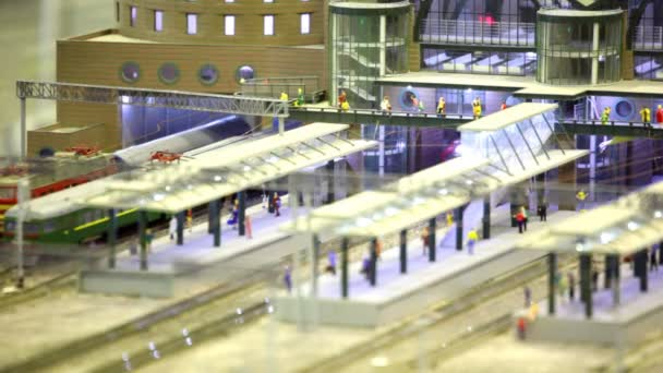 In modern toy city passenger train passes by rail through platform in station