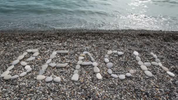 surfovat pláži nápis z kamenů v oblázkovou pláž s mořem