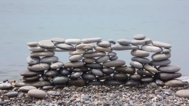 zeď z kamenů na oblázkové pláže, modré moře surfování v pozadí