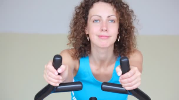 Portrait of happy young woman training on gym apparatus