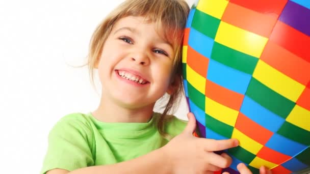 lány átfogja játék varicoloured levegő labdát és a mosoly, fehér háttér