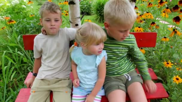 four kids seating on the bench in the yard