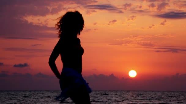 silueta mladé tančící ženy na pláž, moře při západu slunce a obloha v pozadí