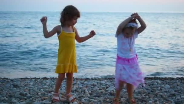 Twee kleine meisjes dansen in avond kiezel strand zee op