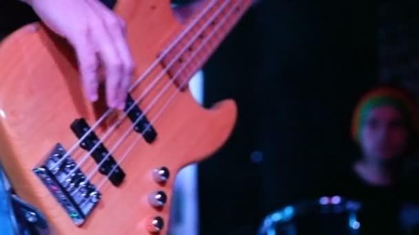 azonosítatlan basszusgitáros zenész él a színpadon