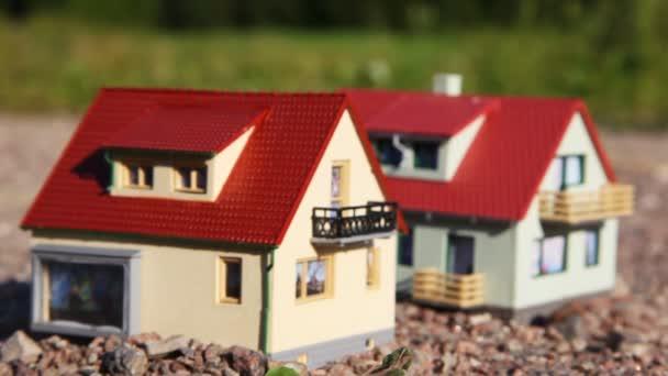 két kis játék ház, piros tetejű állni a kövek park