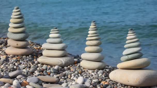 Kő verem a kavicsos tengerpart, hullámzó tenger a háttérben