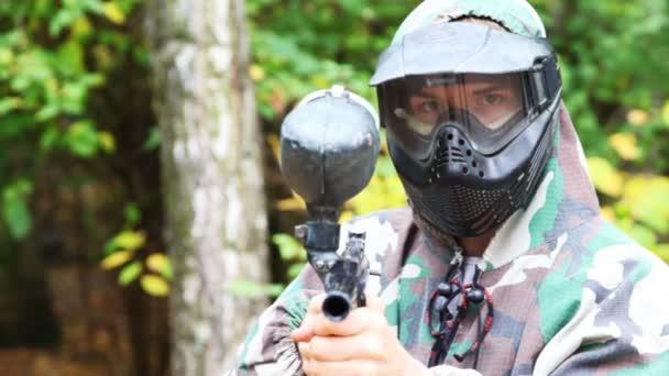 muž v helmě a maska s paintball zbraň cíle v kameře