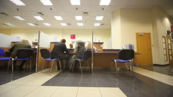 sedí v židle klientů při konzultaci v bance