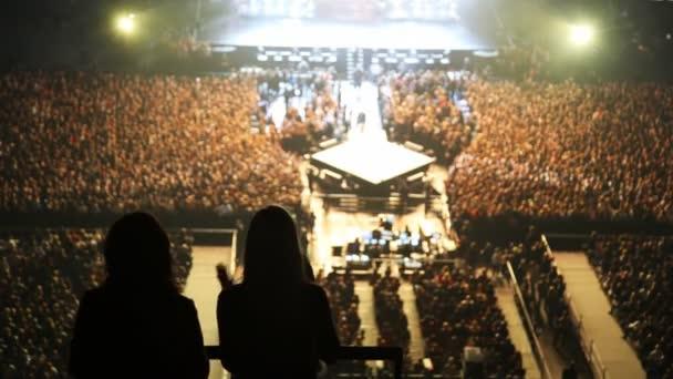 siluety dvou tančících žen proti scéně v koncertním sále
