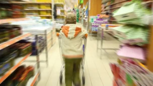 chlapec s nákupní vozík, v supermarketu, kamera za ním