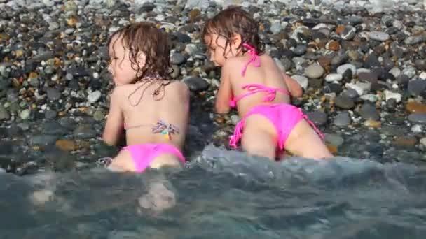 dvě šťastné malé holčičky, které leží na oblázkové pláži s mořem surfovat