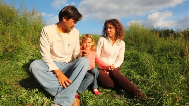 familj från mor, far och dotter sitter på grön kulle i park