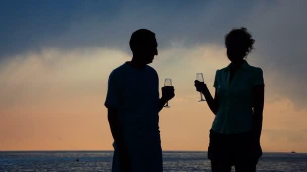 Silhouetten von Mann und Frau mit Bechern Champagner trinken und küssen