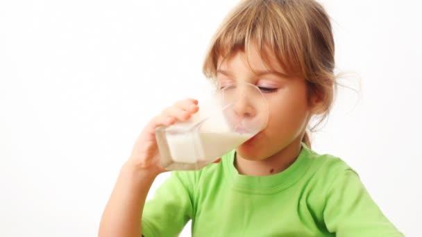 malá holka pije mléko ze skla a nastartuje bubliny v něm