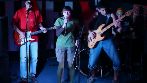 musical group of four persons live on stage in club