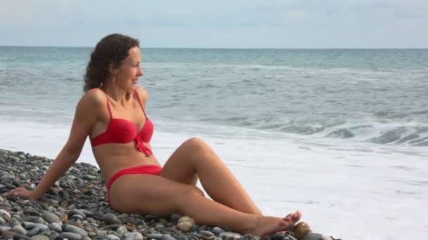 mladá žena sedící na oblázkové pláži, surfování vlny moře, v pozadí