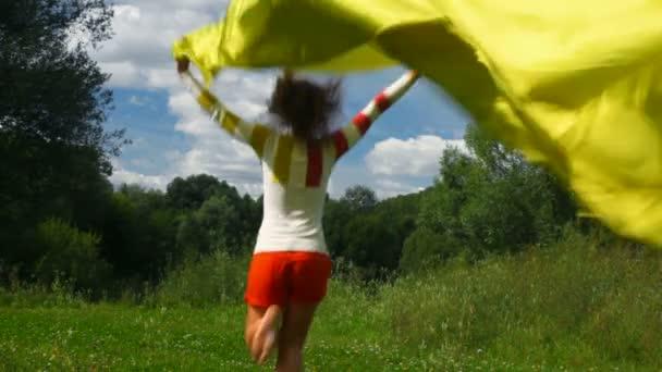 mladá krásná žena s žlutého hedvábí běží v letním parku z fotoaparátu