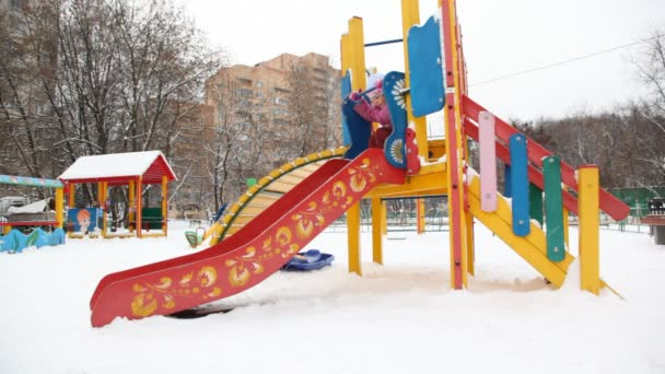 kleine Mädchen spielen auf Folie in Stadt Spielplatz, Winter