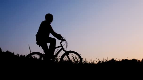 Silhouette of man riding bicycle stops against sky