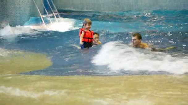 Boy escapes from clutches of woman, man and quickly runs away from pool in indoor waterpark