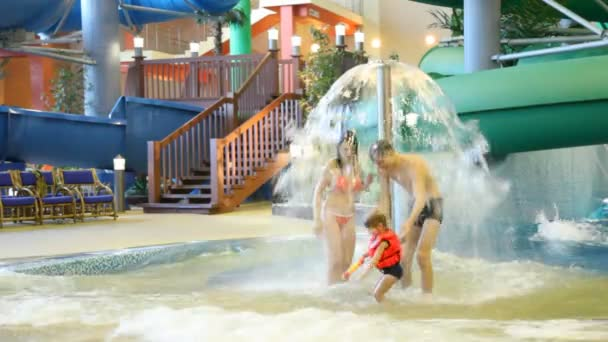 Charming woman, man and girl with a water gun stand under a fountain in water park