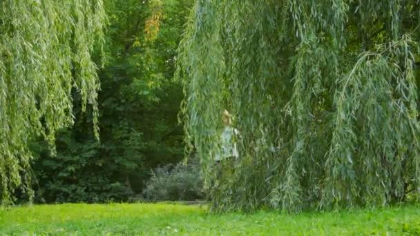 šťastná rodina 4 osoby běží v parku zpoza stromu do fotoaparátu