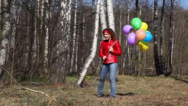 šťastná mladá žena s balónky vede k fotoaparátu v jarní březovým grove