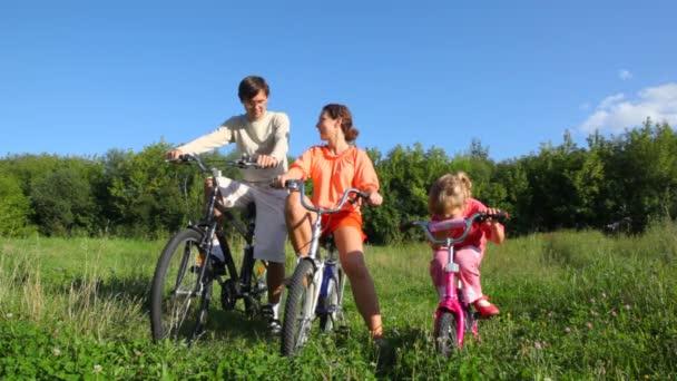 rodina s dcerou sedí na jízdní kola a rozhovory