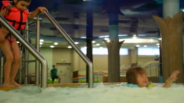 Boy and girl jump one by one in jacuzzi bubbling water in water park