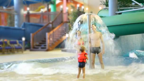 Charming woman and man stand under fountain, and girl shoot at them with water gun in water park