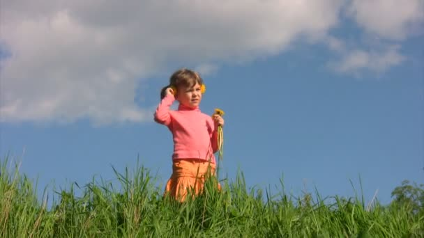 Girl with field flowers stands in meadow against sky